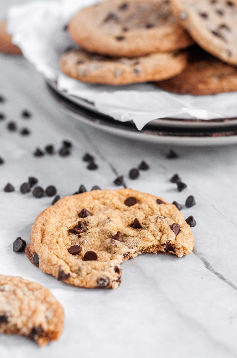 A chocolate chip cookie laying on a talbe surrounded with mini chocolate chips. There is a large bite taken out of the cookie and a small plate of cookies sitting in the background.