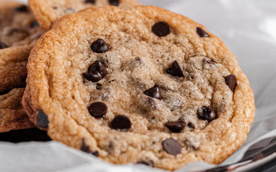 A close up of a chocolate chip cookie full of mini chocolate chips sitting on a plate with other chocolate chip cookies.