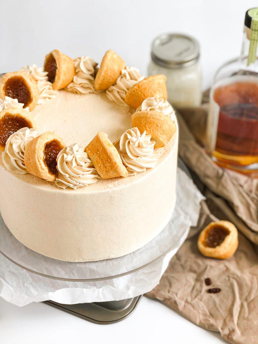 A butter tart cake with soft brown sugar frosting and topped with mini butter tarts and frosting swirls.