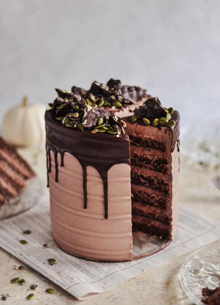 A cake covered in a chocolate frosting with a chocolate drip going over the edge and a slice cut into it.