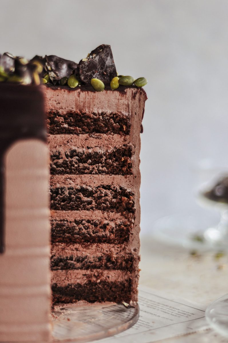 The inside shot of a cake covered in chocolate frosting and six layers of pumpkin cake.