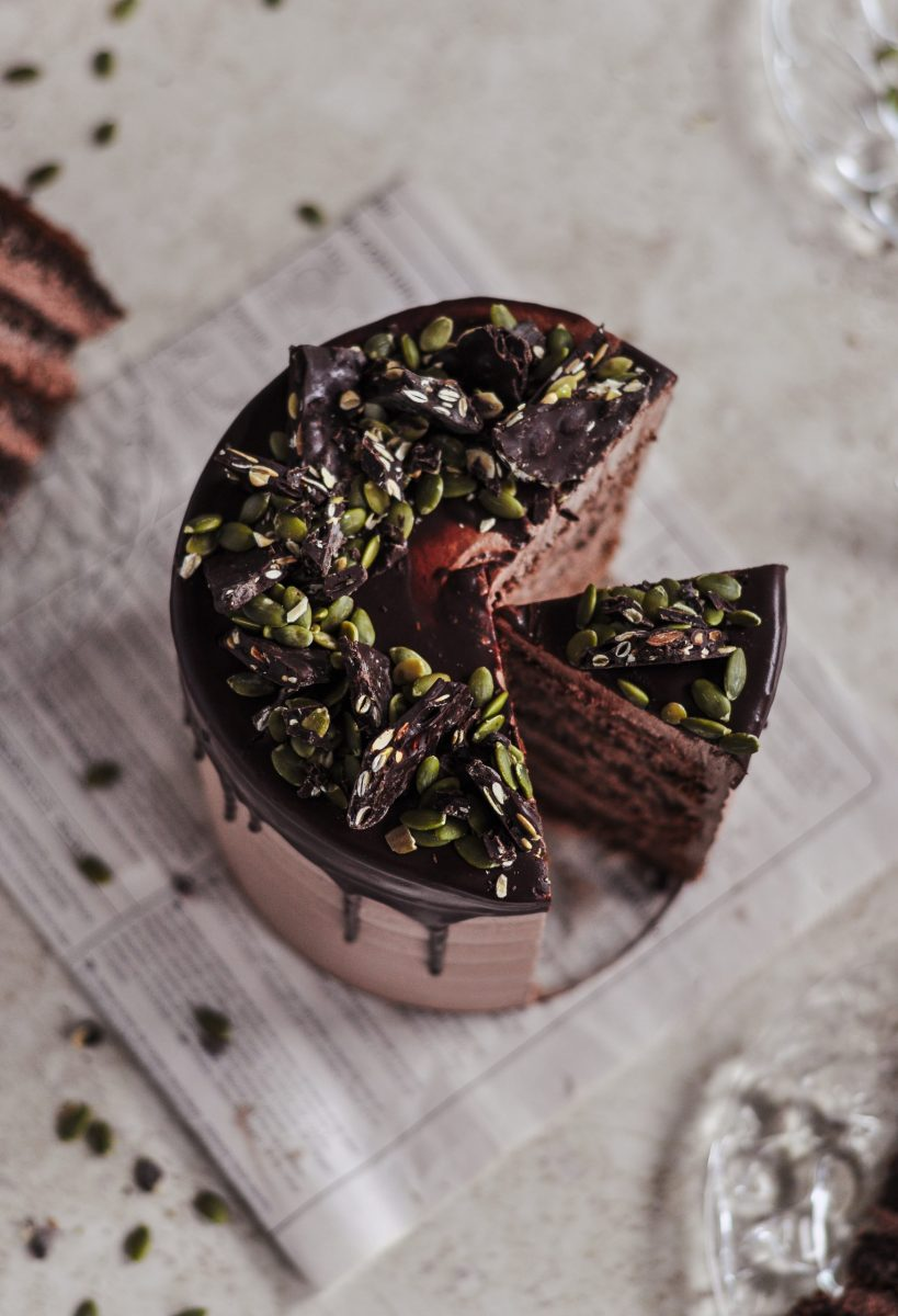 The top view of a chocolate cake covered in green pumpkin seeds and pieces of dark chocolate.