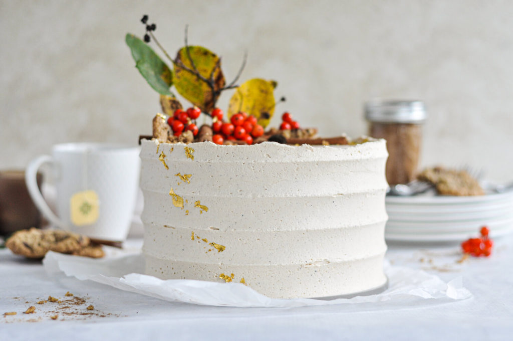A textured cake with gold on one side and branches and berries as decor.