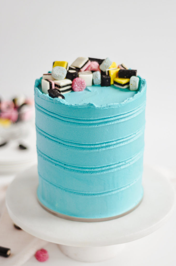 Blue cake with all-sorts black licorice candies on top