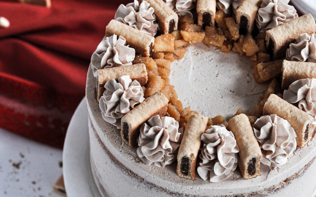 A cake topped with cinnamon frosting buttercream swirls and a fig newton between each swirl.