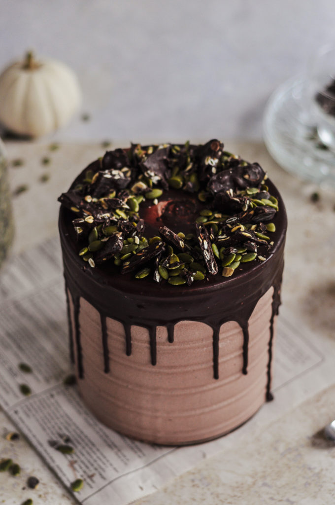 A chocolate cake with a chocolate drip over the edges and topped with pumpkin seeds.