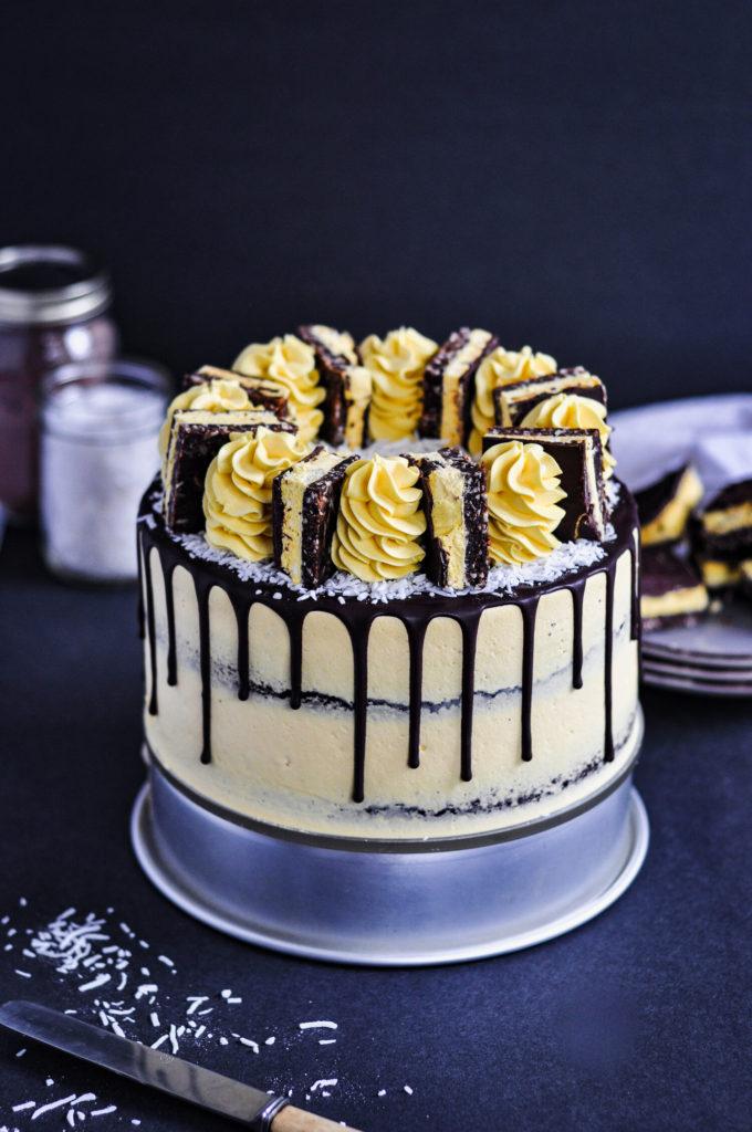 Yellow cake with a chocolate drip and nanaimo bars on top