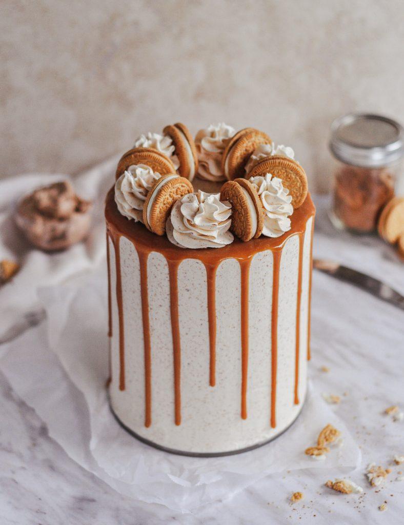 Cinnamon bun inspired cake with oreos on top and buttercream swirls.
