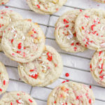 sugar cookies laying on a cooling rack with red sprinkles.
