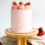 A light pink cake topped with buttercream swirls and strawberry slices