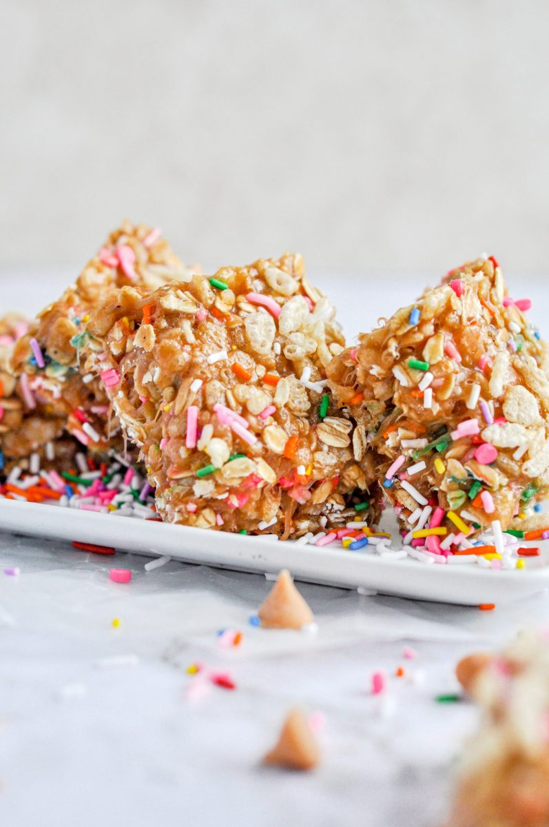 Brightly sprinkled rice krispy oat bars on a small white plate