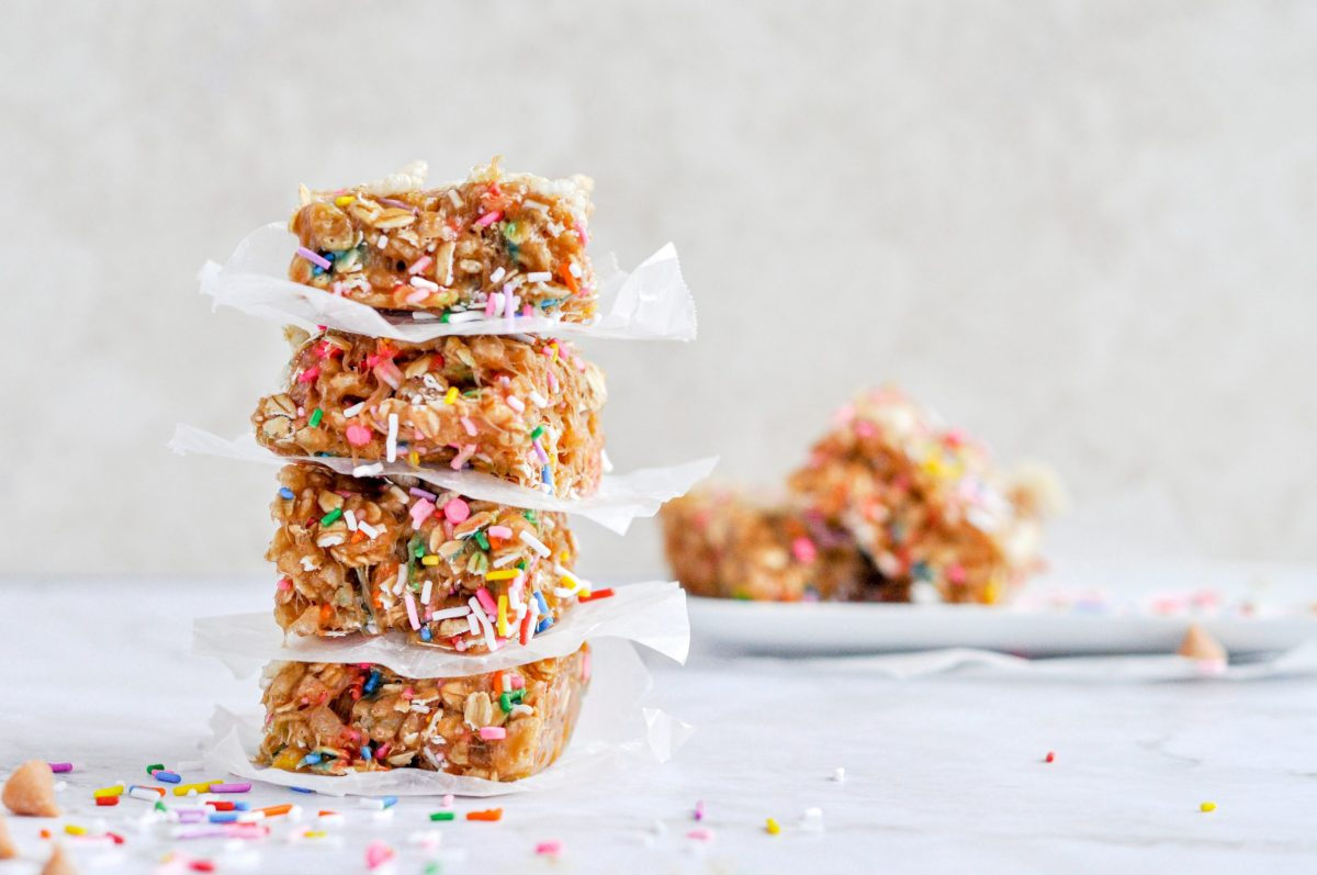 A stack of brightly sprinkled butterscotch rice krispy bars in the foreground with a few bars in the background.