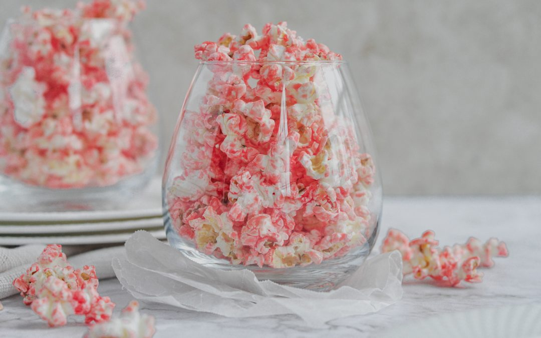 a gass full of pink popcorn