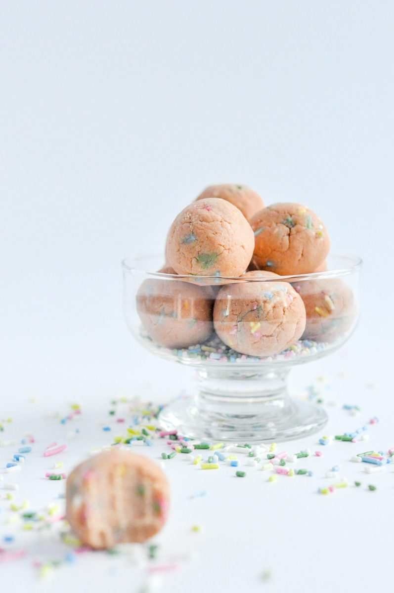 A small glass bowl full of protein balls with sprinkles