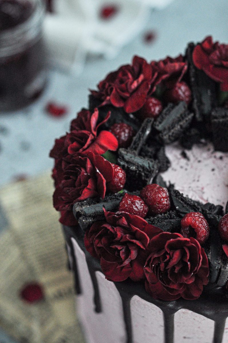 Close up picture of red carnations and dark chocolate oreos on top of a cake