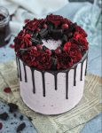 A pink cake with a chocolate drip and dark red carnation flowers on top