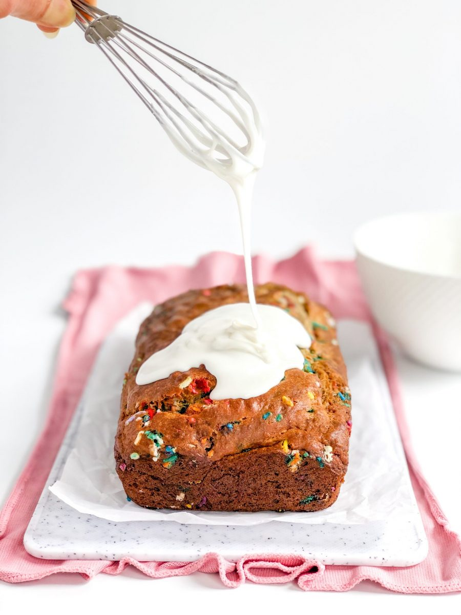 A load of funfetti banana bread with a glaze being dripped on it.