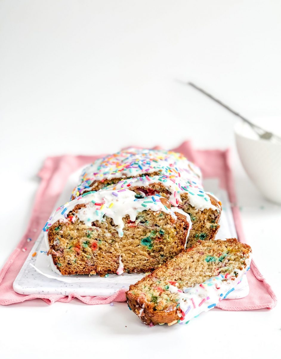 A load of funfetti banana bread on a white cutting board all sliced up