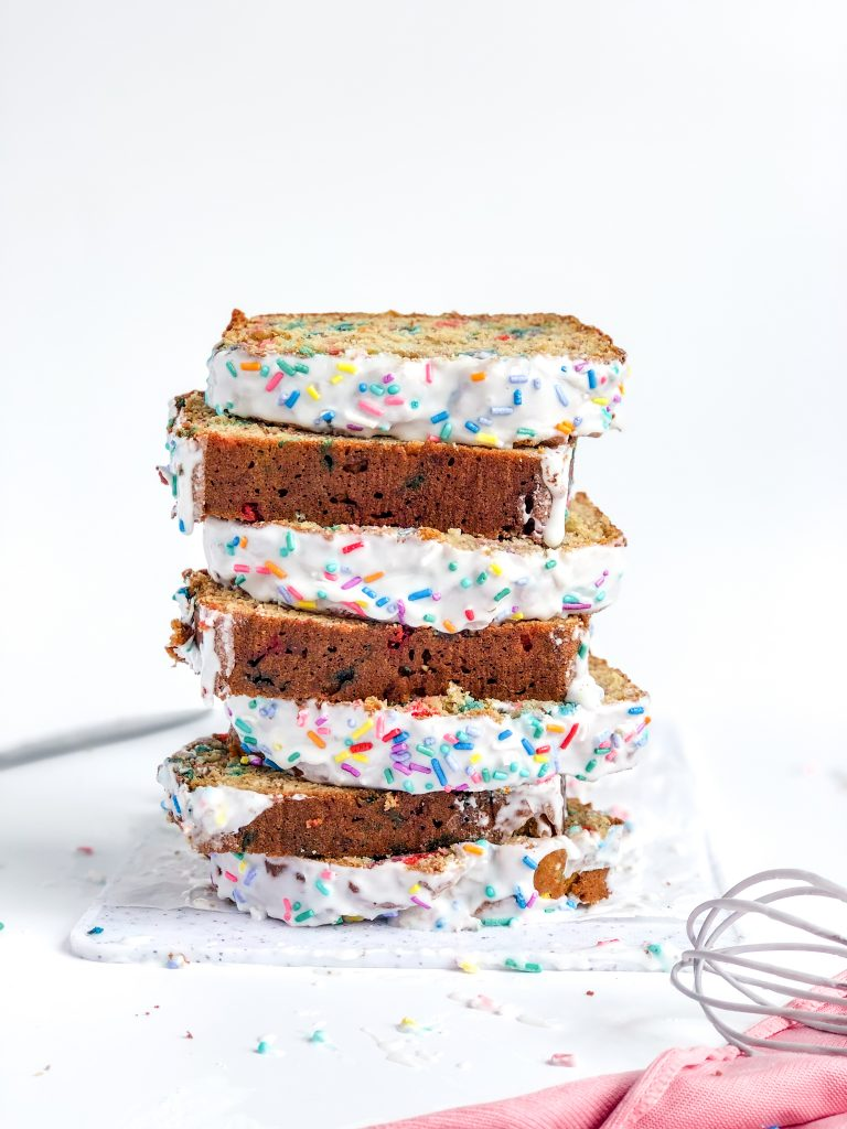 a stack of sprinkled banana bread slices with a white glaze