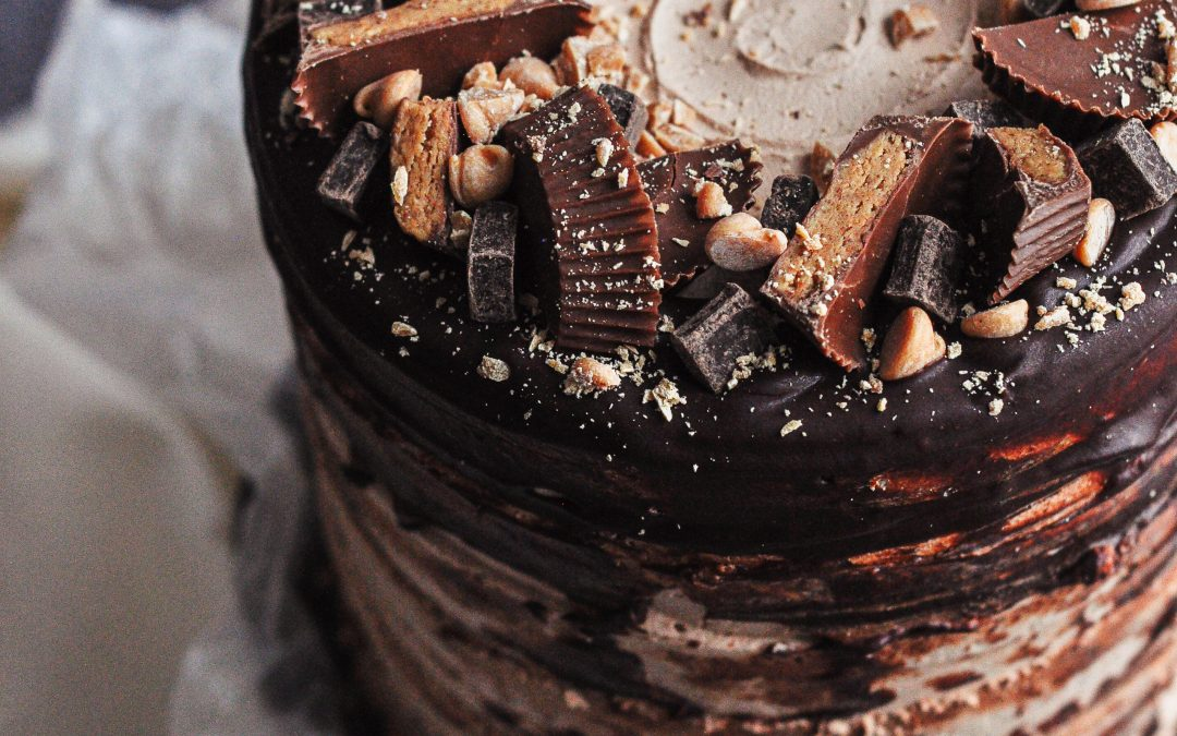 A chocolate cake covered in a rustic dark chocolate ganache and topped with all sorts of chocolates and peanuts.