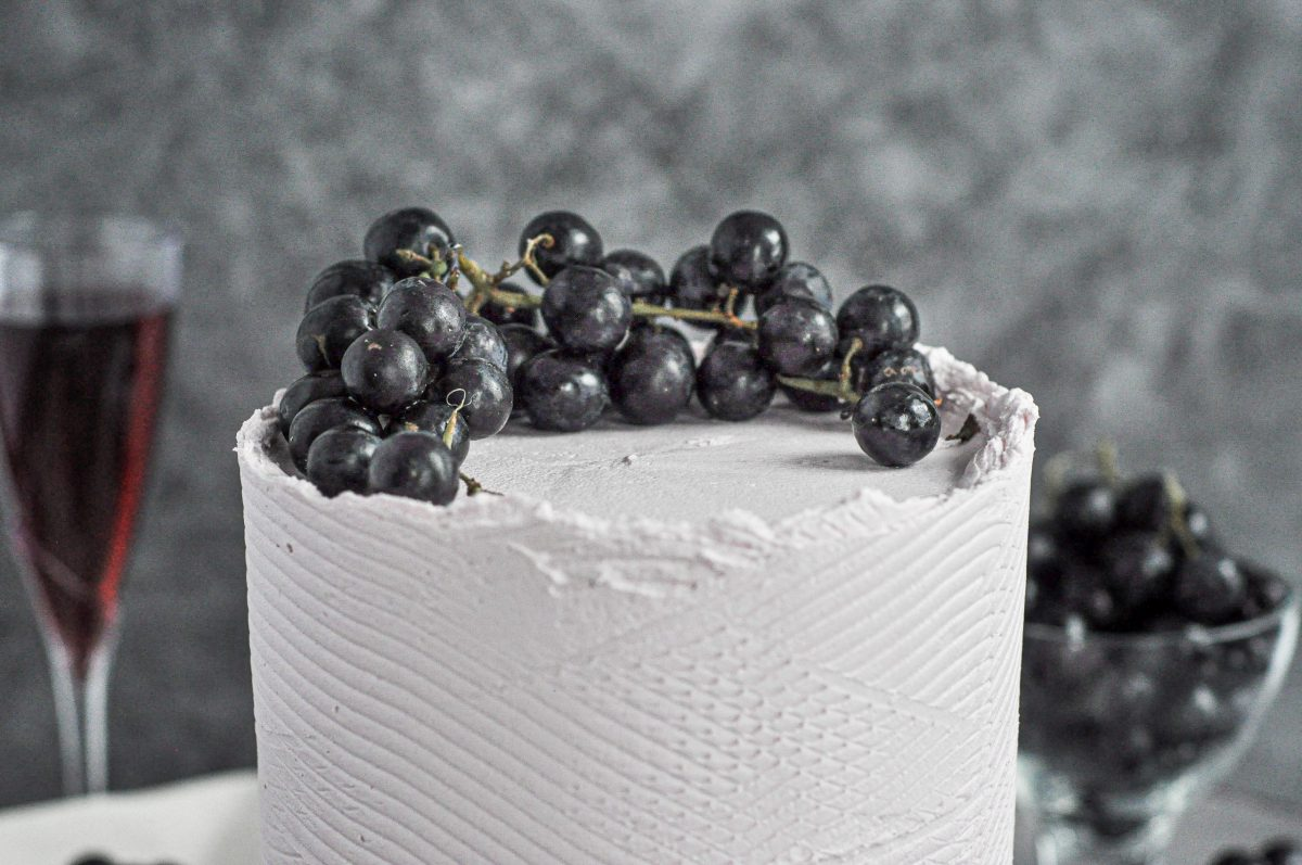 The top of a light purple cake with black grapes on top