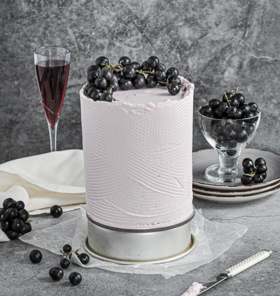 light purple cake with grapes on top
