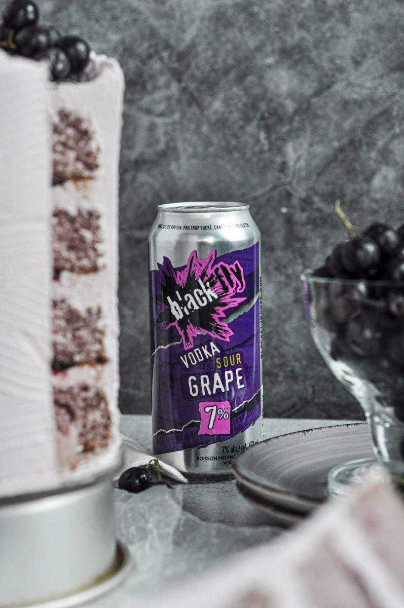 A silver and purple can of Black Fly Booze Vodka Grape Sour drink between a bowl of black grapes and a sliced cake