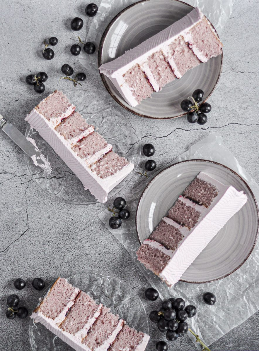 Four slices of light purple grape cake styled on plates and black grapes around the plates