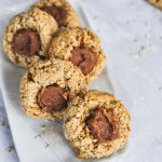 a row of staggered thumbprint almond butter cookies on a small plate