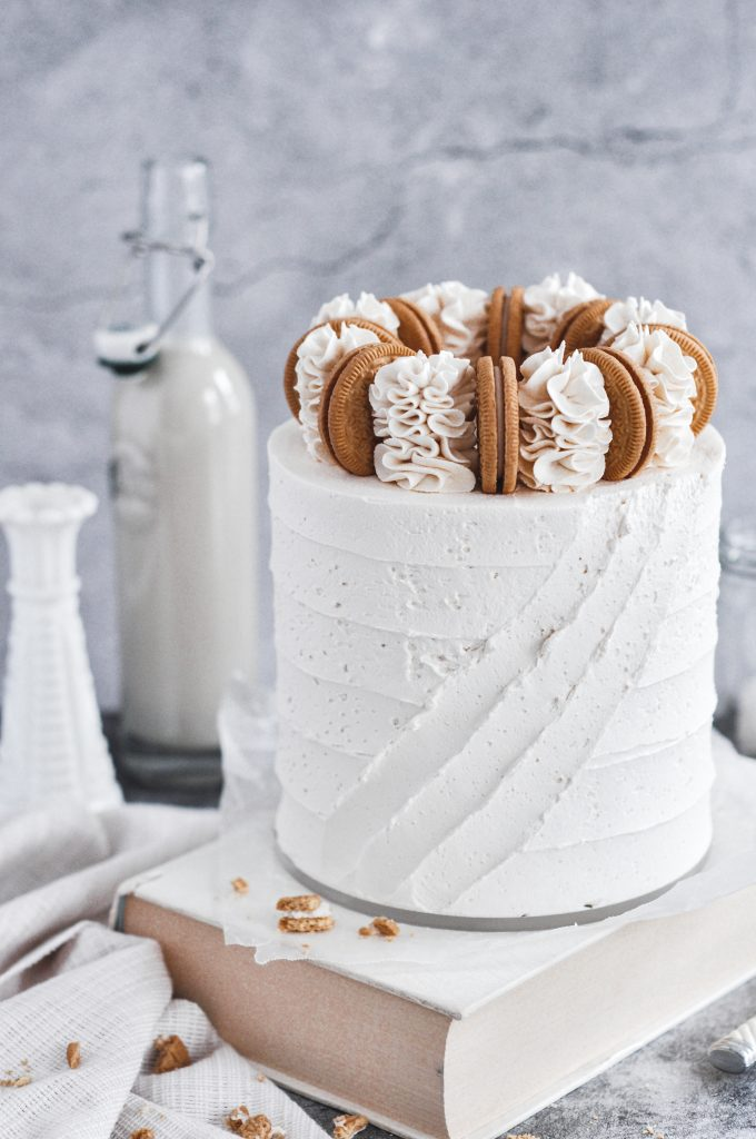 A white vanilla cake with diagonal stripes in the frosting.