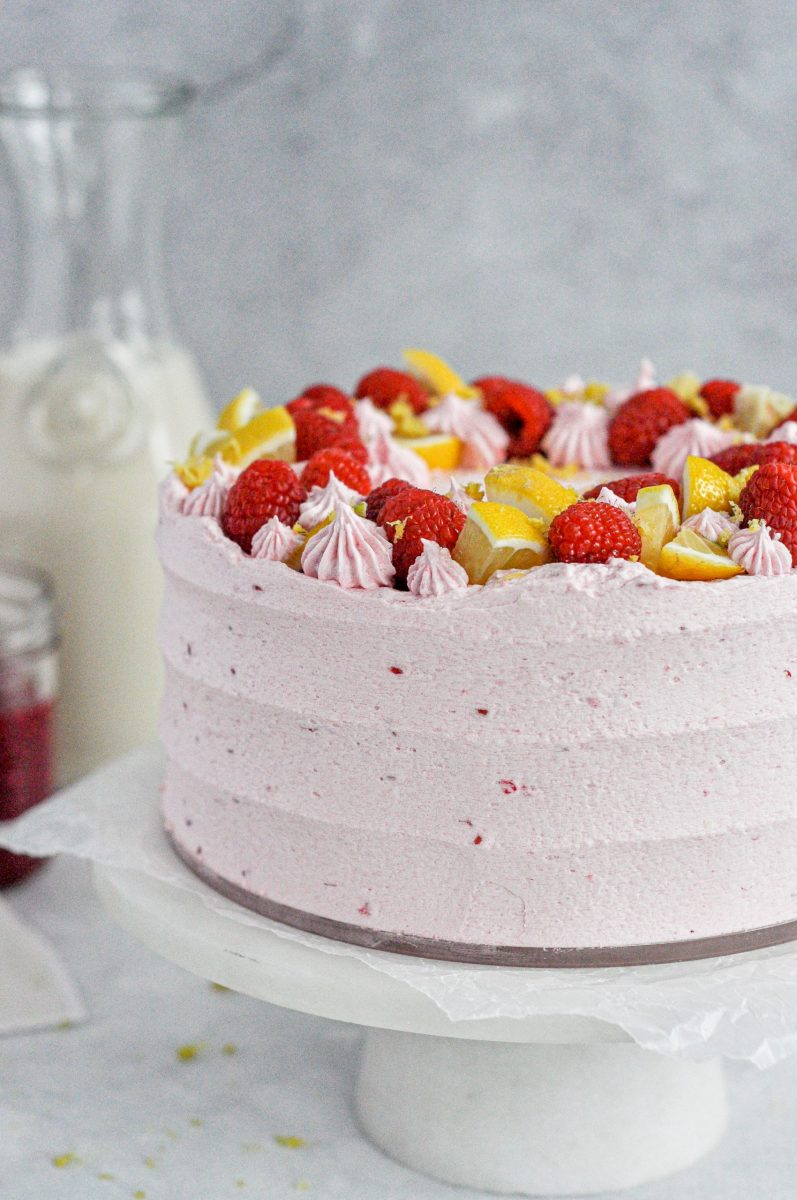 A light pink lemon raspberry cake topped with fresh raspberries and lemon slices.
