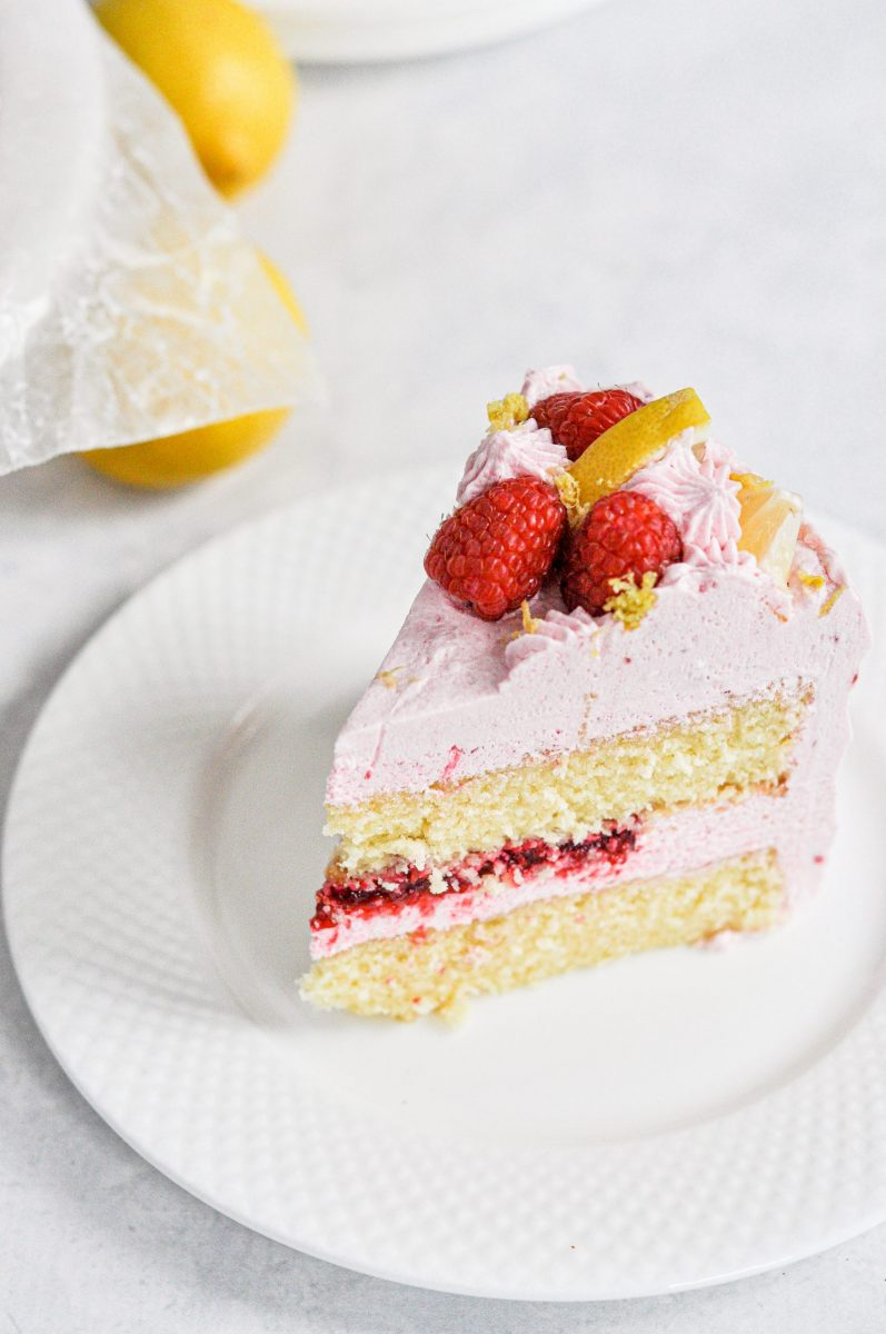 A slice of lemon cake with raspberry filling and topped with fresh raspberries and lemon slices