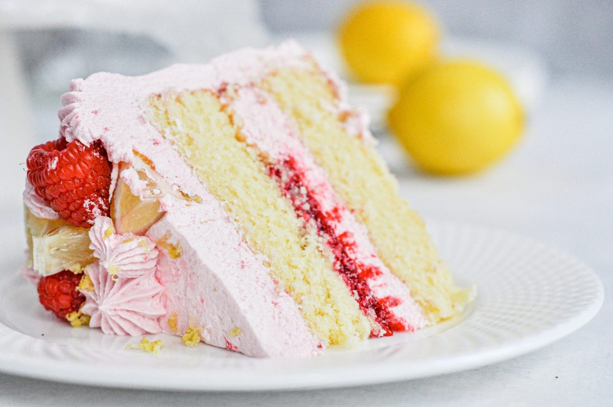 A close-up picture of a slice of lemon cake with raspberry filling and a light pink frosting.