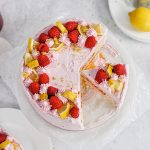 A lemon raspberry cake with a slice cut out of it and topped with fresh raspberries and lemon wedges.