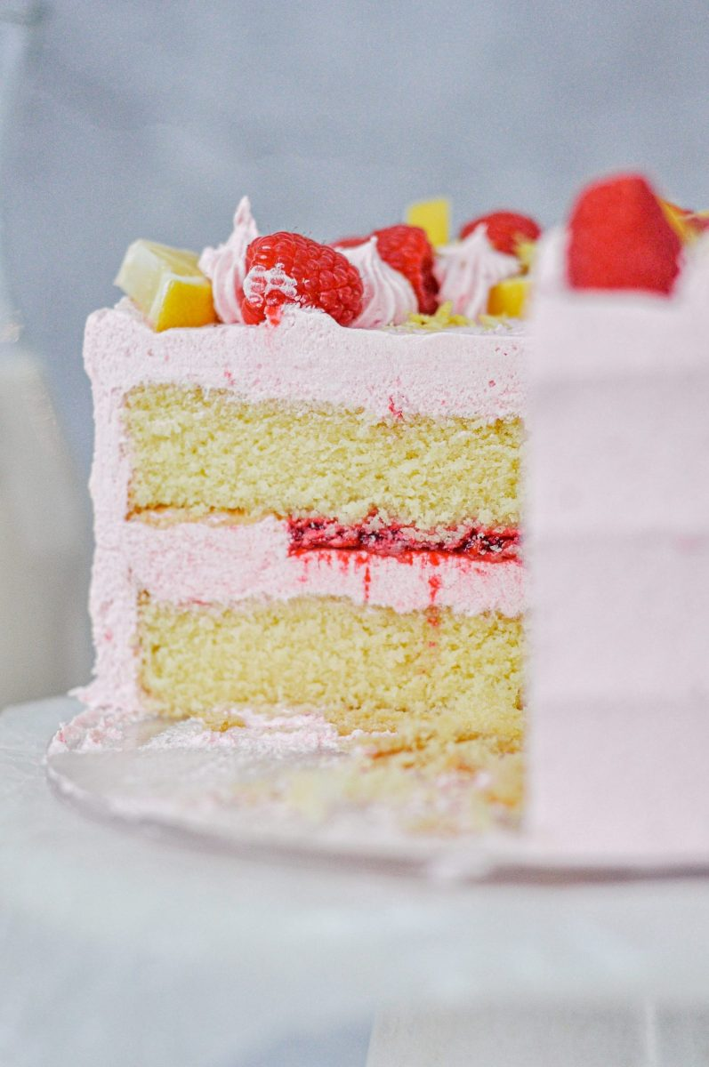 A light pink cake with the inside layers showing and filled with bright pink raspberry filling.