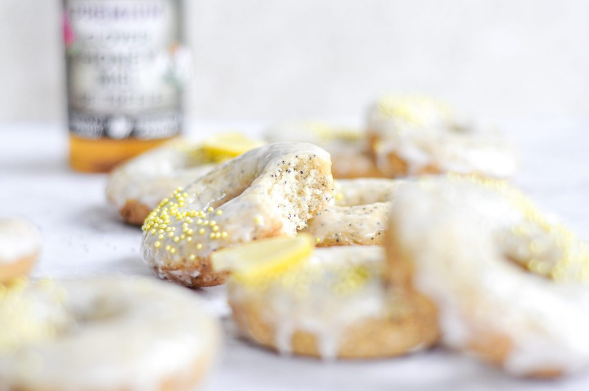 A close-up shot of a lemon poppy seed donut with a white glaze on top, yellow sprinkles, and a bite taken out of it.