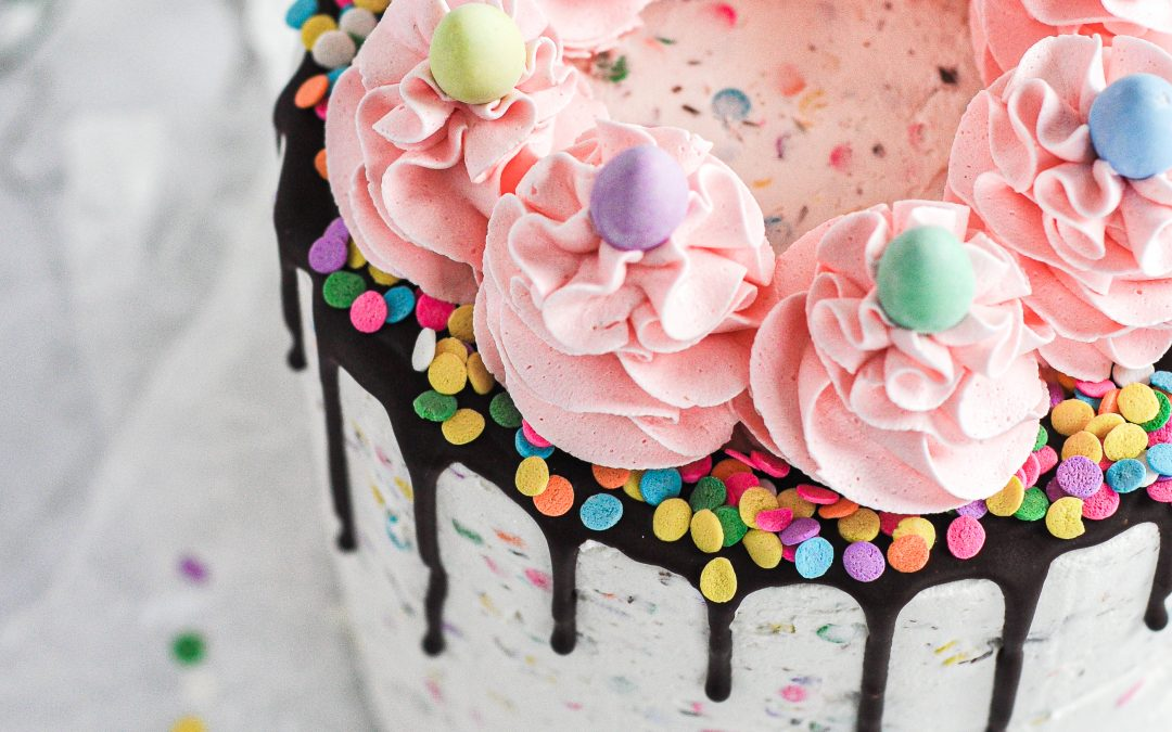 A speckled mini egg cake with a chocolate drip and pink frosting swirls on top decorated with pastel chocolate mini eggs.