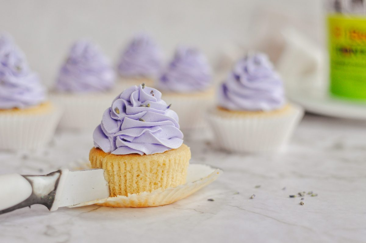 A honey cupcake topped with purple frosting and a knife cutting through it.