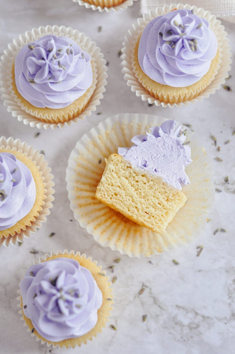 A honey cupcake sliced in half and laying on it's side with purple frosting on top.
