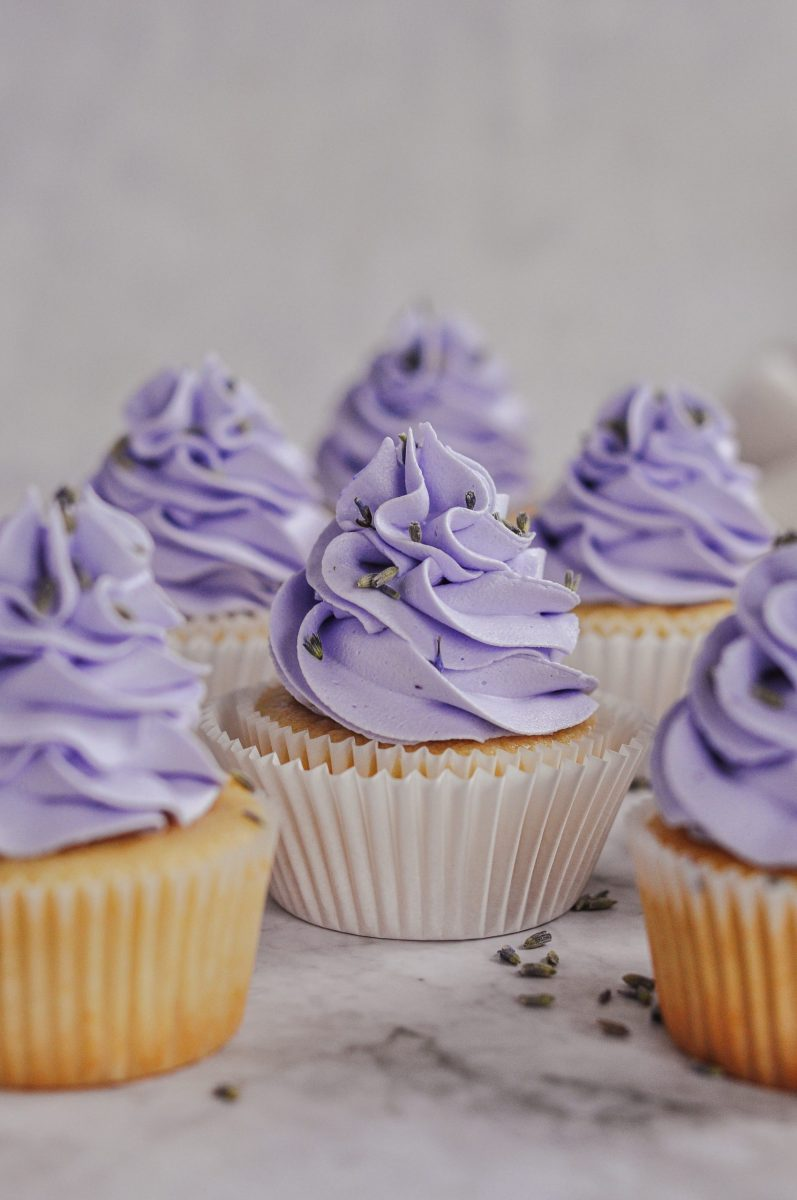 Honey cupcakes with a light p[urple frosting swirl on top.