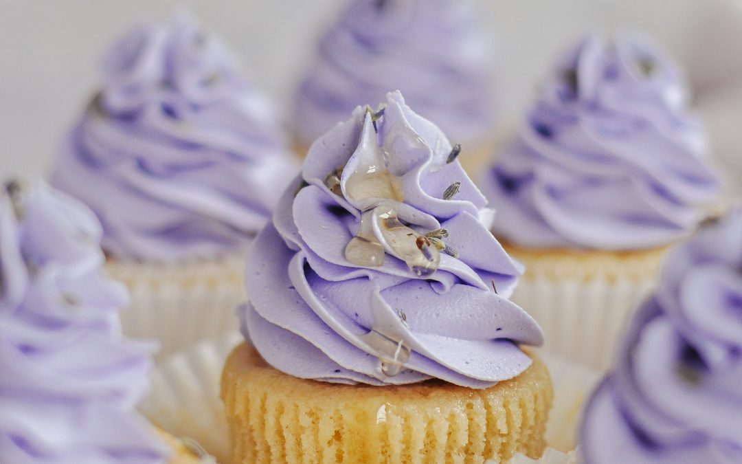 Light purple cupcakes with a drizzle of honey on the frosting