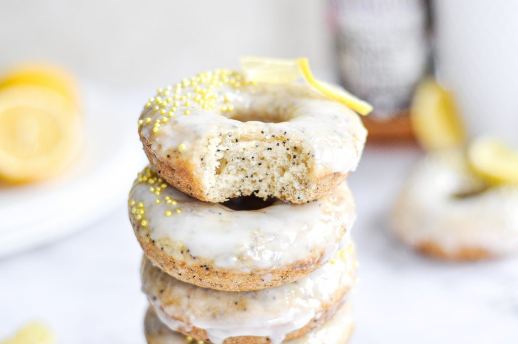 poppy seed donuts with a white glaze and yellow sprinkles on top.