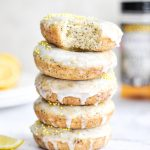 A stack of baked lemon poppy seed donuts with a white glaze and yellow sprinkles on top.