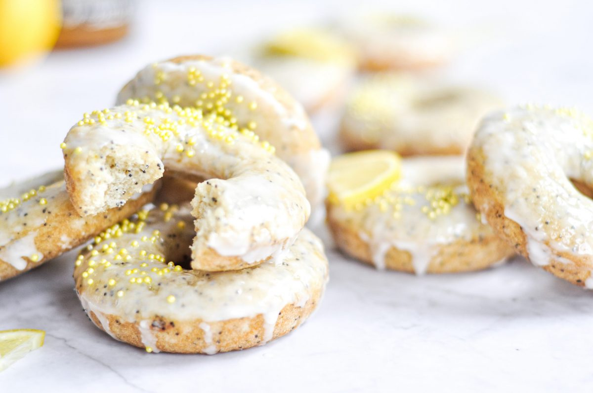 A close-up of baked lemon poppy seed donuts with yellow sprinkles and one donut has a bitye taken out of it.