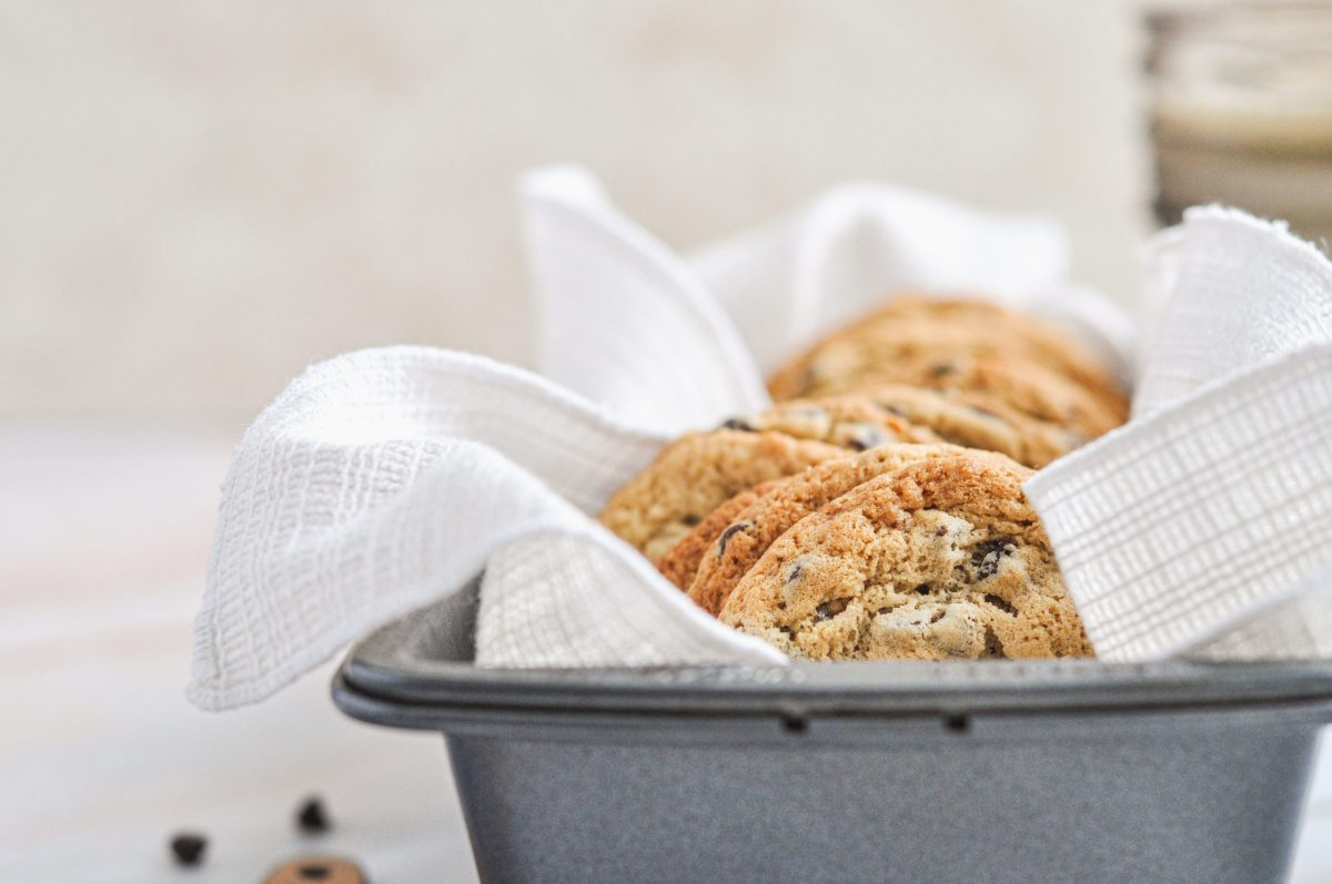 Peanut butter chocolate chip cookies sitting in a bread pan with a white linen underneath