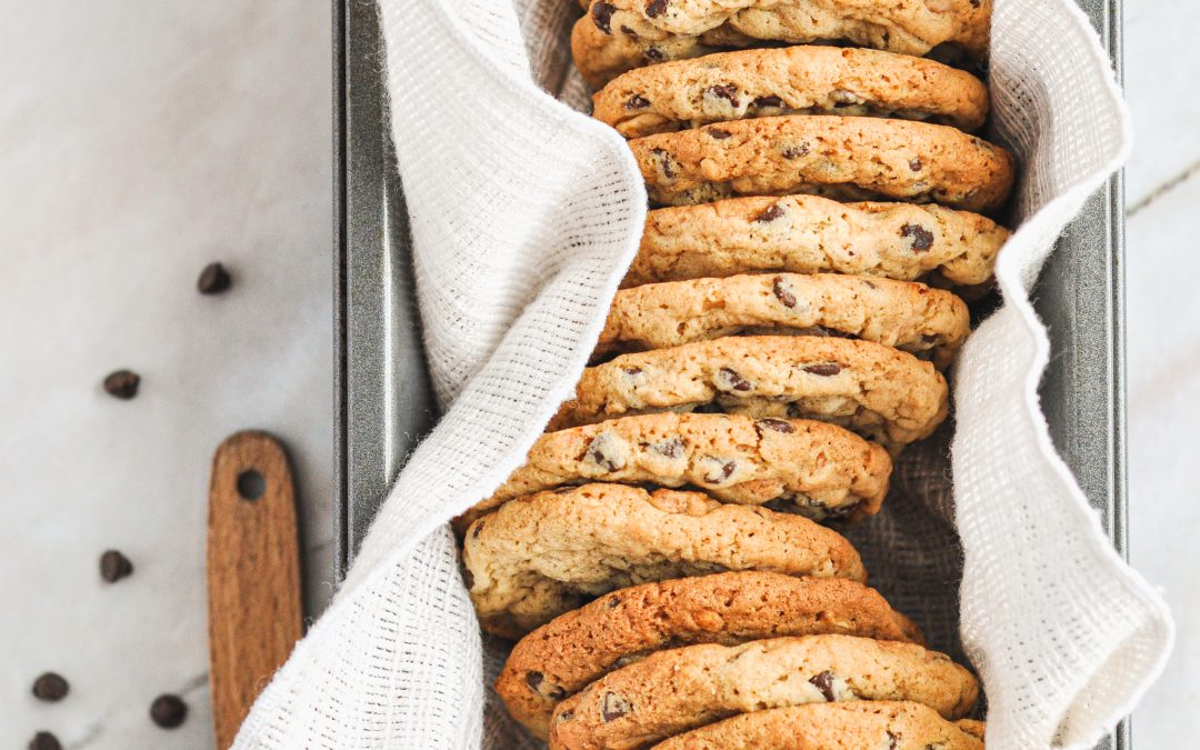 A row of peanut butter chocolate chip cookies in a bread pan on top of a white linen
