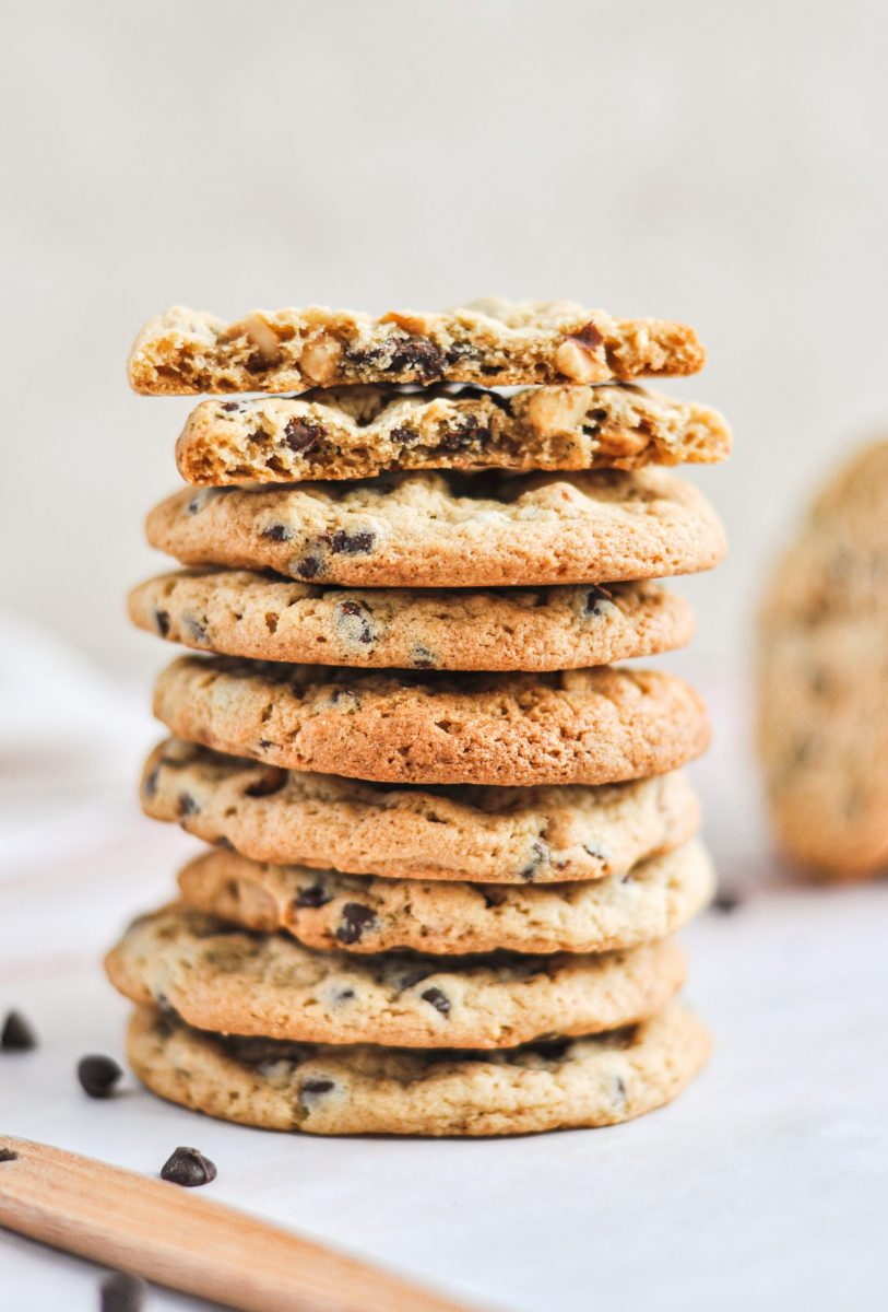 A stack of golden peanut butter chocolate chip cookies with the top cookie broken in half