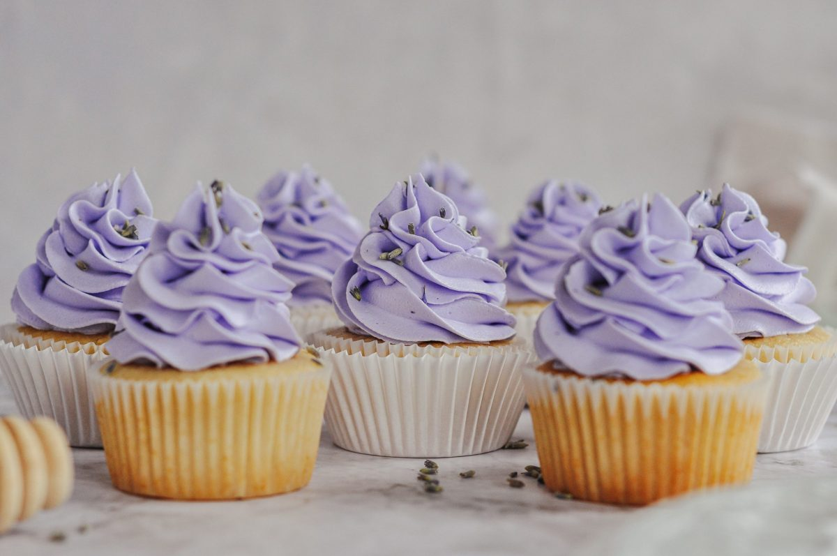 A line up of honey cupcakes with light purple frosting swirls on top.