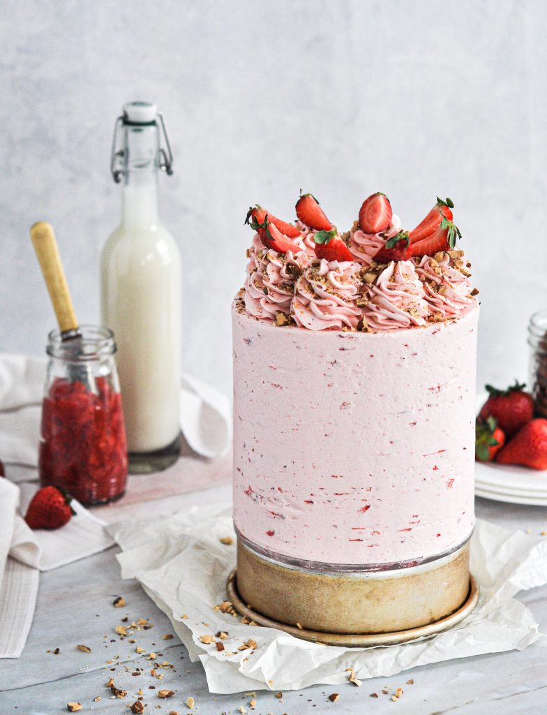 A light pink frosted cake topped with frosting swirls and strawberries