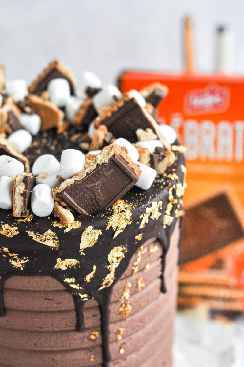 A close up shot of a s'mores cake top with mini marshmallows and chocolate covered cookies on top.